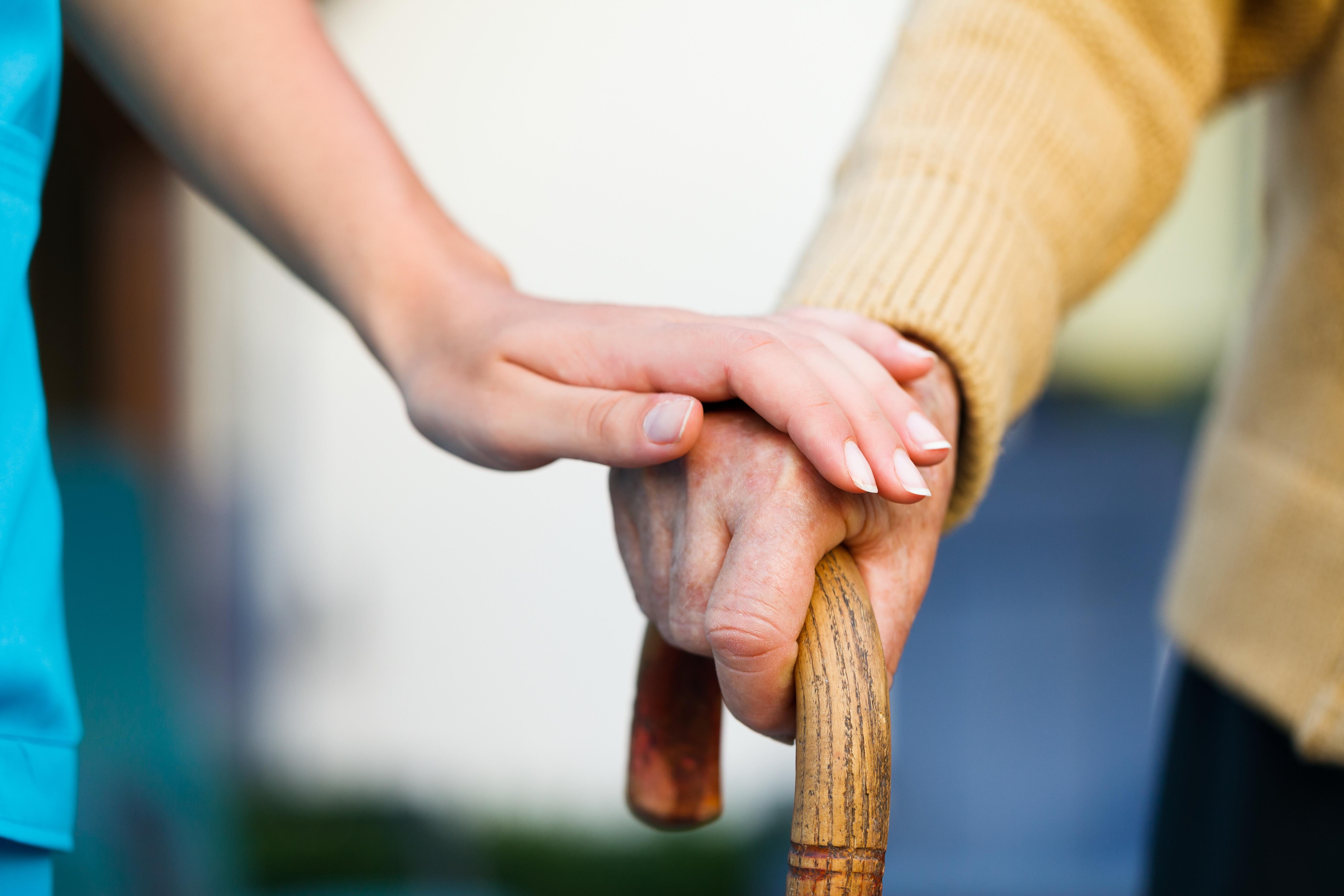 Das Bild zeigt eine Hand einer älteren Person, die sich auf einem Gehstock abstützt. Die Hand einer jüngeren Person (vermutlich die einer Pflegerin) liegt behütend auf der Hand der älteren Person.