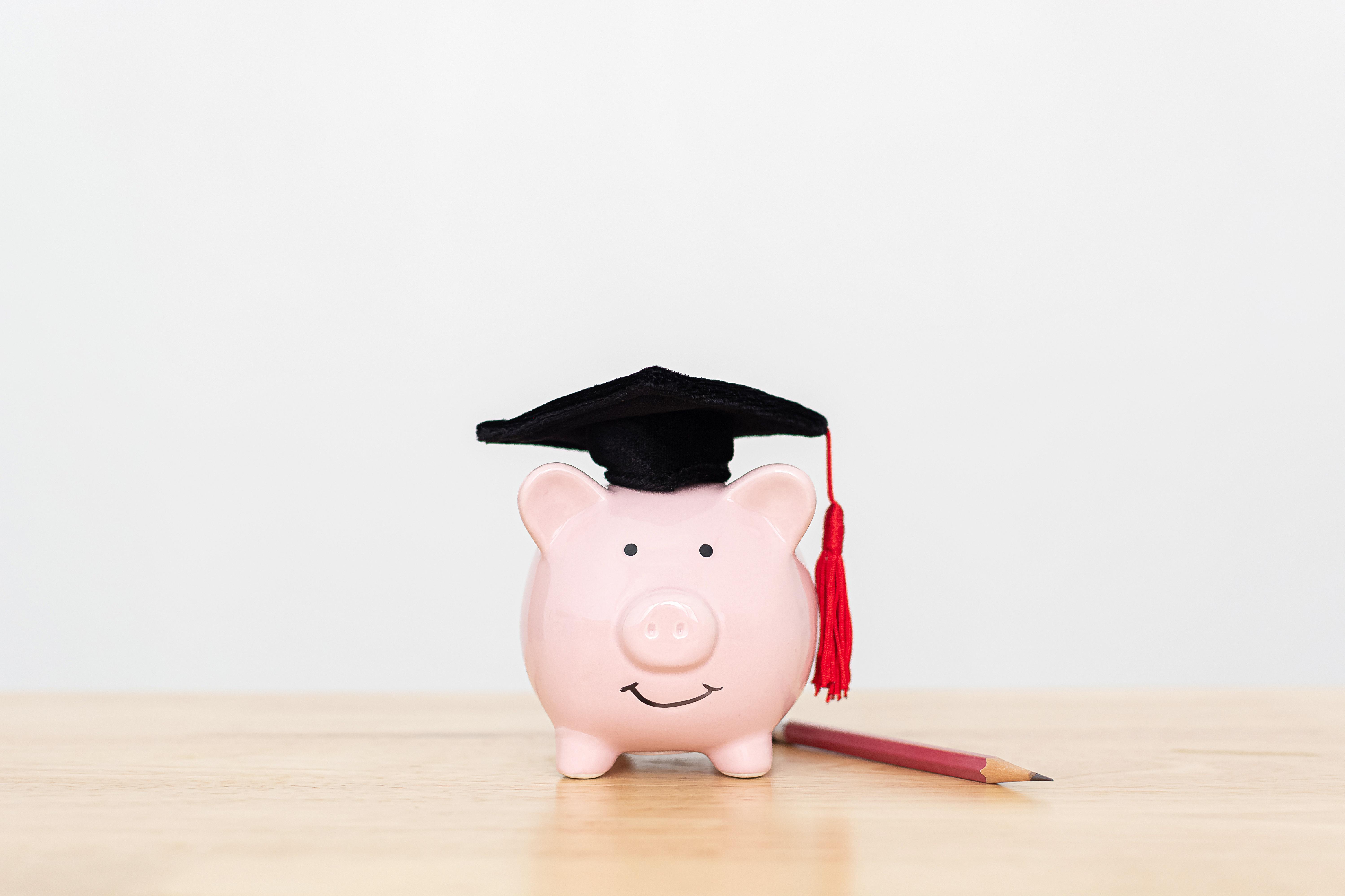 Ein rosafarbenes Sparschwein steht auf einer hellen Holzfläche. Es hat zwei schwarze Augen und einen lachenden Mund aufgemalt. Auf dem Kopf trägt es eine Absolventenkappe. Neben ihm liegt ein Holzbleistift.