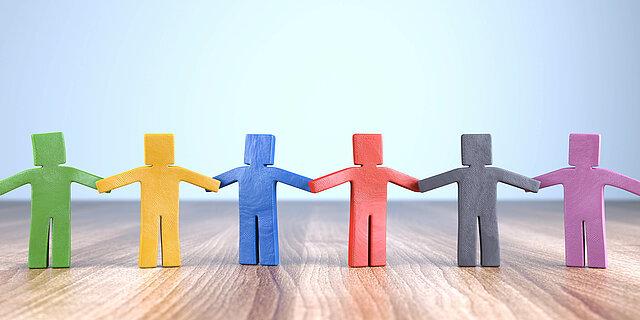 Das Bild zeigt sechs bunte, kantige Knetfiguren, die sich die Hände reichen und eine Kette bilden.