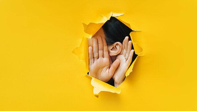 zu sehen ist eine gelbe Bahn aus Papier, an einer Stelle ist ein Loch gerissen, hinter dem Loch ist das der Kopf einer Frau im Seitenprofil zu sehen, die sich beide Hände rechts und links neben die Ohren hält um zu lauschen