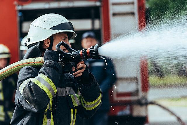 Auf dem Bild ist ein Feuerwehrmann in Schutzausrüstung zu sehen, der zum Löschen einen Schlauch und ein Strahlrohr auf der Schulter hält. Im Hintergrund steht ein Feuerwehrfahrzeug mit geöffnetem Geräteraum und weitere Feuerwehrmänner.