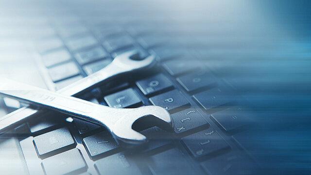 Das Bild zeigt den Ausschnitte einer Computertastatur auf der zwei überkreuzte Maulschlüssel liegen. Es symoblisiert digitale Werkzeuge.