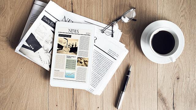 Das Bild zeigt die naurbelassene Oberfläche eines Holztisches. Auf dem Tisch liegen übereinander eine Zeitung, ein Tablet und eine Lesebrille. Daneben befindet sich ein Stift und eine Tasse Kaffee.