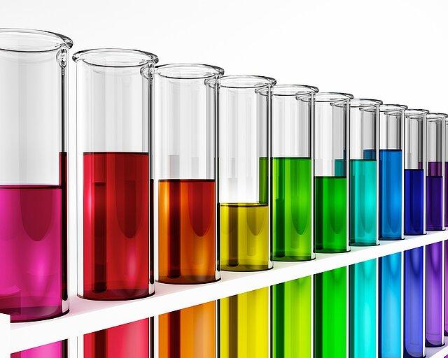 Zu sehen ist ein Reagenzglashalter mit einer Vielzahl an Reagenzgläsern. Diese sind verschiedenfarbigen Flüssigkeiten unterschiedlich hoch gefüllt.