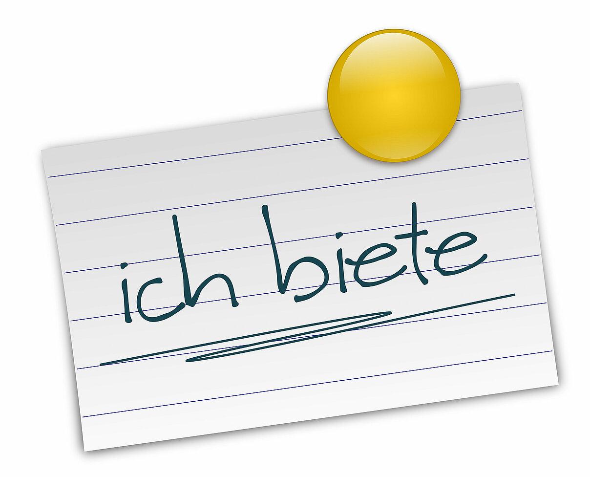 """Zu sehen ist weißer Notizettel mit einer gelben Reißzwecke in der rechten oberen Ecke. Auf dem Zettel steht handschriftlich """"ich biete""""."""