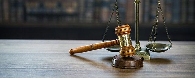 Im Vordergrund ist eine Holztischplatte zu sehen. Auf ihr steht eine mechanische Balkenwaage und ein Richterhammer aus Holz mit entsprechendem Gegenstück. Sie symbolisieren die Justiz. Im Hintergrund steht ein Bücherregal.