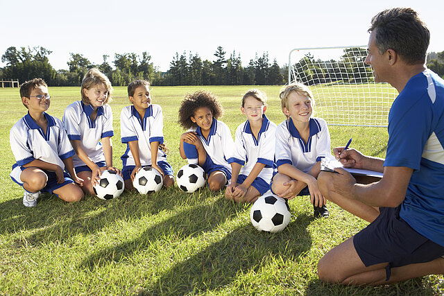 Das Bild zeigt einen Fußballtrainer der mit einer Gruppe von Kindern auf dem Rasen kniet. Die Kinder tragen weiß-blaue Trikots – vor ihnen liegen Fußbälle. Er erklärt der Gruppe etwas mit Hilfe einer Schreibkladde und eines Stiftes den er in der Hand hält, während die Kinder zuhören.